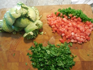 Scoop out the avocado, finely chop tomatoes and jalapeños, and cut up the cilantro while marinating the onion mix.