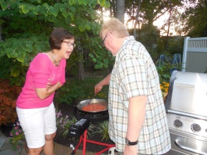 Karen Mortka is amazed over the fact that Russ is grilling a paella!