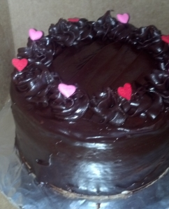 A delicious chocolate ganache cake with heart decorations.