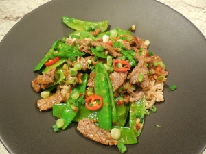 Plated Chili Beef Stir Fry with Scallions and Snow Peas over brown rice.