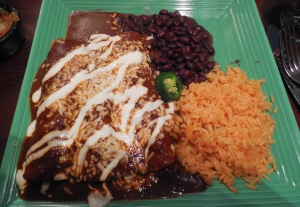 Steak Enchiladas al Mole - served with a thick, rich chocolate tinged sauce made from chilies and exotic spices served over rice with black beans